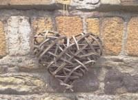 Aus Weiden geflochtenes Herz am Haus in FR